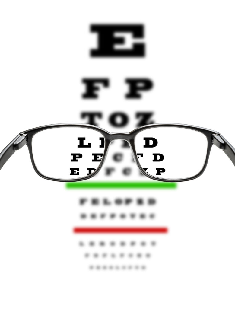 Front view of a black frame eyeglasses with an eye chart test at the background